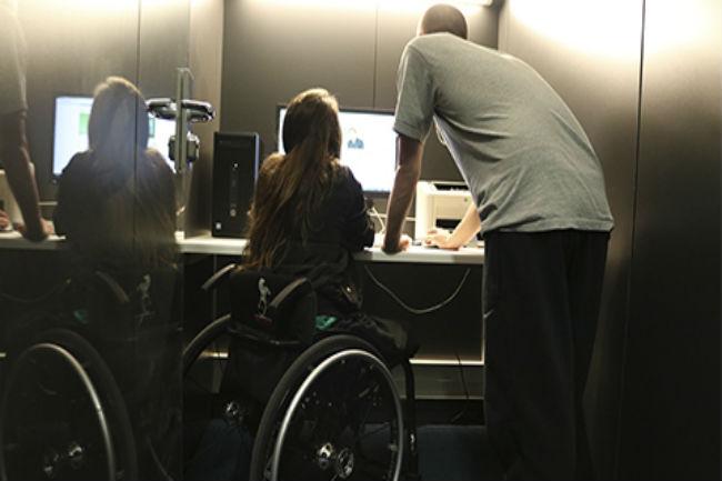 noia amb cadira rodes davant un ordinador