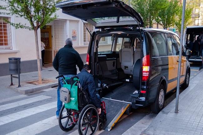 persona en cadira de rodes entrant a un taxi