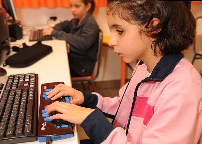 nena amb discapacitat visual estudiant amb un ordinador
