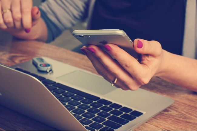 persona amb un ordinador y un telèfon mòbil